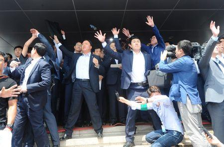 Security personnels try to protect South Korean Prime Minister Hwang Kyo-ahn (obscured) from bottle and eggs thrown by angry residents in Seongju where a U.S. THAAD anti-missile defense unit will be deployed, South Korea, July 15, 2016.  News1/Lee Jong-hyun/via REUTERS