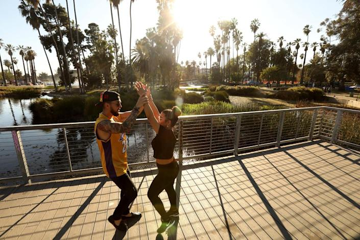 A man in a Lakers jersey and a woman dance on a platform next to a lake