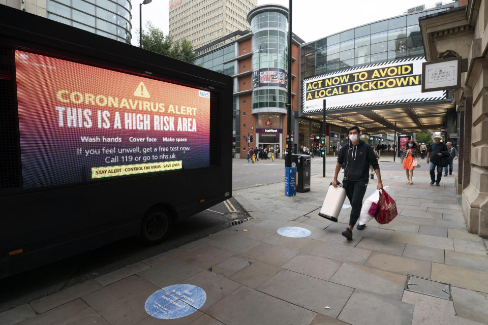 "Members of the public are seen by public information messages in central Manchester after Prime Minister Boris Johnson set out new restrictions to last ""perhaps six months"" to slow the renewed spread of coronavirus, Manchester, England, Tuesday Sept 22, 2020. The UK has reached ""a perilous turning point"", Boris Johnson said as he set out a raft of new coronavirus restrictions for England. ( AP Photo/Jon Super)"