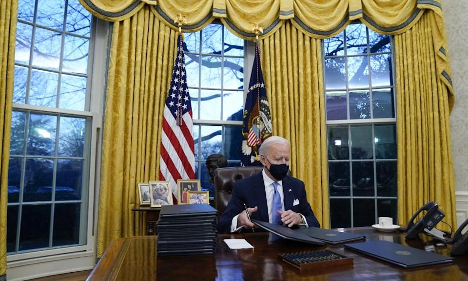 Joe Biden signs his first executive orders in the Oval Office of the White House on 20 January.
