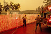 Firefighters engage in structure defense as the Dixie Fire burns in Chester, Calif., on Wednesday, Aug. 4, 2021. The region is under red flag fire warnings due to dry, windy conditions. (AP Photo/Noah Berger)