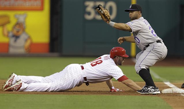 Philadelphia Phillies' Darin Ruf is safe on a pick-off attempt at first as Colorado Rockies first baseman Willin Rosario catches the throw during the second inning in a baseball game, Wednesday, Aug. 21, 2013, in Philadelphia. (AP Photo/Laurence Kesterson)