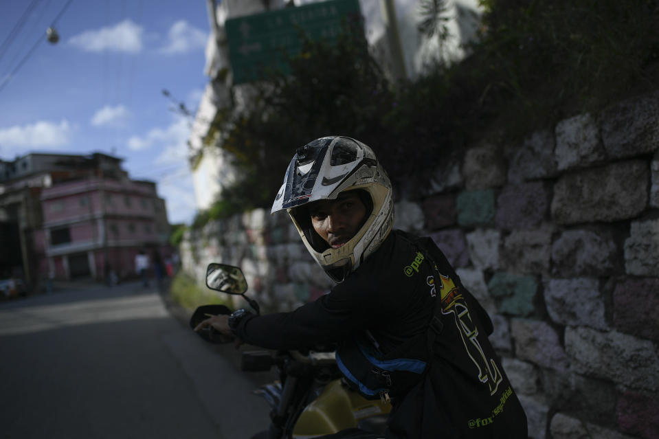 """Motorcycle stuntman Pedro Aldana waits for his friends for an exhibition in the Ojo de Agua neighborhood of Caracas, Venezuela, Sunday, Jan. 10, 2021. The motorcycle trick rider and adrenalin junkie who prefers the nickname """"Crazy Pedro,"""" draws masses of Venezuelans starved for entertainment to his shows across the country. (AP Photo/Matias Delacroix)"""