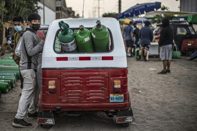 Men queue to refill empty oxygen tanks it in Villa El Salvador, on the southern outskirts of Lima