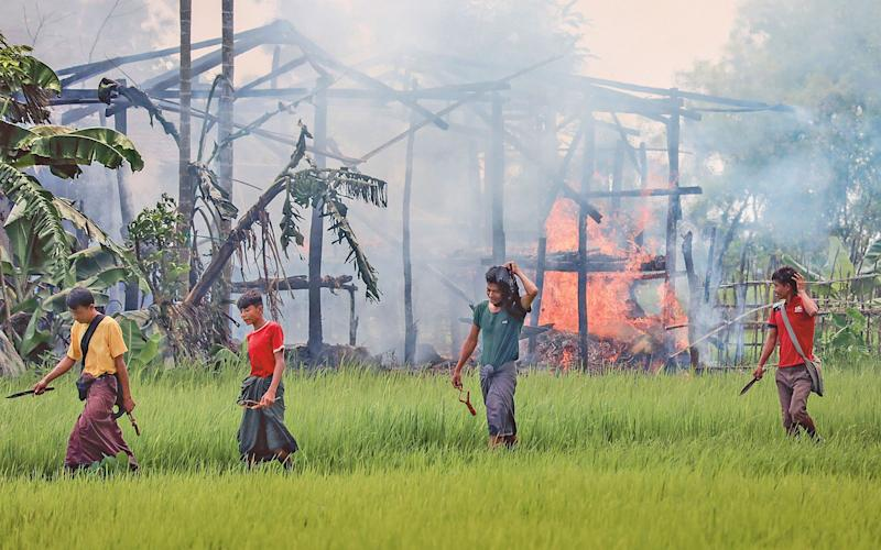Unidentified men carrying knives and slingshots walk past a burning village near Maungdaw in Rakhine state, on 7 September, 2017. Many Rohingya have died trying to flee the fighting, not making it to the refugee camps in Bangladesh - This content is subject to copyr