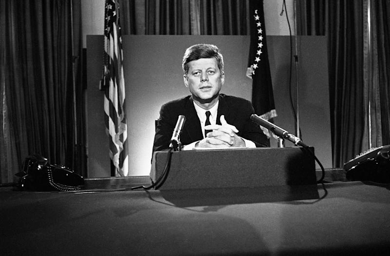 FILE - In this July 26, 1963 file photo, U.S. President John F. Kennedy sits behind microphones at his desk in Washington after finishing his radio-television broadcast to the nation on the nuclear test ban agreement initialed by negotiators in Moscow. (AP Photo/John Rous)