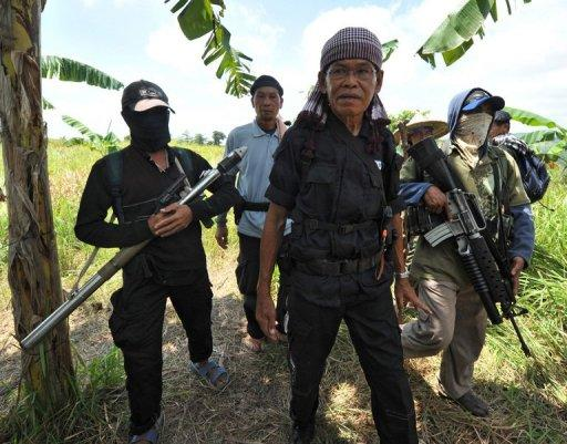 Ameril Umbrakato (C), leader of a breakaway Muslim separatist group, pictured here with his troops in Datu Unsay town, Maguindanao province, in August. Umbrakato, whose forces have threatened the peace efforts of the government, has fallen ill, a spokesman for his group said on Saturday