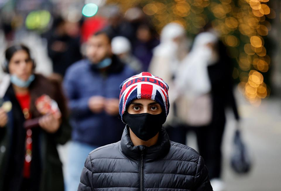 A pedestrian wearing a face mask or covering due to the COVID-19 pandemic, and a Union flag-themed hat walks along Oxford Street in central London on December 22, 2020. - UK government borrowing continued to soar in November on emergency action to support the virus-hit economy which nevertheless rebounded stronger than expected in the third quarter, official data showed Tuesday. Government borrowing last month hit £31.6 billion ($41.8 billion, 34.2 billion euros), a record for November -- taking public sector net debt to £2.1 trillion, the Office for National Statistics said in a statement. (Photo by Tolga Akmen / AFP) (Photo by TOLGA AKMEN/AFP via Getty Images)