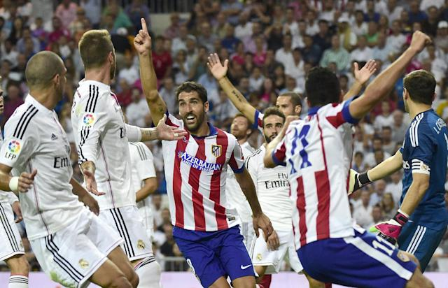 Atletico Madrid's midfielder Raul Garcia (C) celebrates after scoring during the Spanish Supercup first-leg football match Real Madrid CF vs Club Atletico de Madrid at the Santiago Bernabeu stadium in Madrid on August 19, 2014 (AFP Photo/Gerard Julien)
