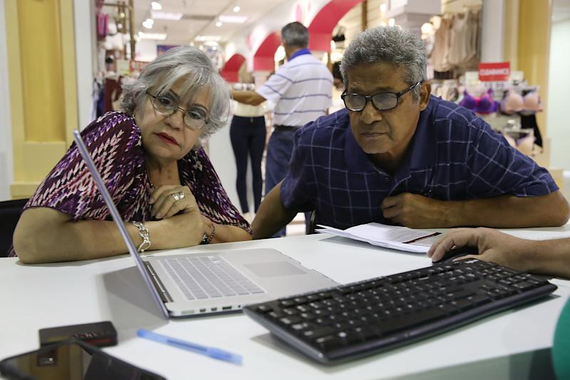 MIAMI, FL - NOVEMBER 01: Isabel Diaz Tinoco (L) and Jose Luis Tinoco look at a computer as Otto Hernandez, an insurance agent from Sunshine Life and Health Advisors, shows them the different insurance plans available under the Affordable Care Act at a store setup in the Mall of Americas on November 1, 2017 in Miami, Florida. The open enrollment period to sign up for a health plan under the Affordable Care Act started today and runs until Dec. 15. (Photo by Joe Raedle/Getty Images)