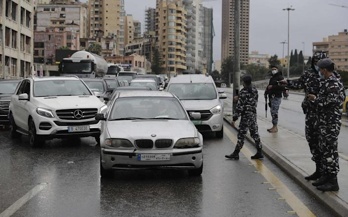 Policemen control cars at a checkpoint in the capital Beirut, as Lebanon enters its first day of strict lockdown - AFP
