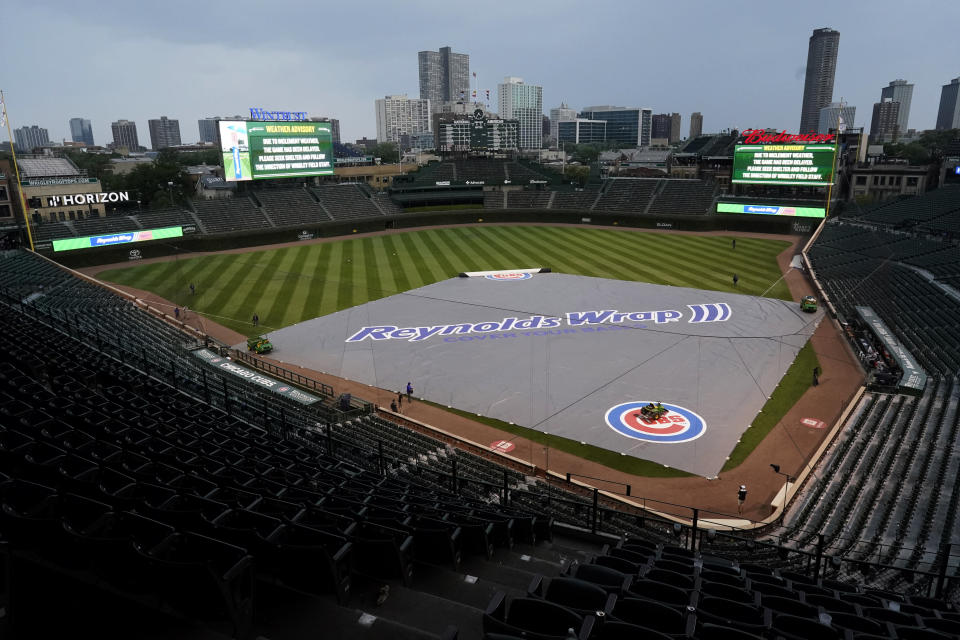 A tarp covers the infield during a rain delay in the ninth inning of a baseball game between the Arizona Diamondbacks and the Chicago Cubs in Chicago, Saturday, July 24, 2021. (AP Photo/Nam Y. Huh)