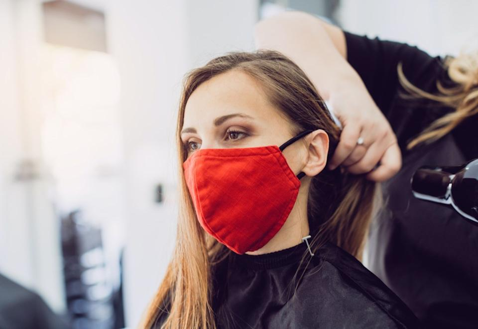 Woman wearing red face mask getting fresh styling at a hairdresser shop