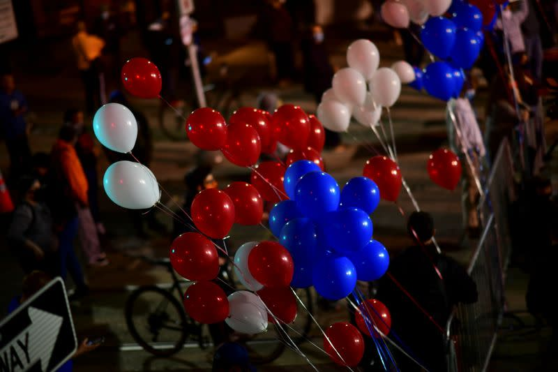 Balloons blow in the wind front of the remaining activists demonstrating across the street from where votes are being counted in Philadelphia