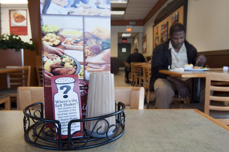 An advisory on salt shakers location in seen on a table at a Boston Market restaurant in Alexandria, Va., Tuesday, May 14, 2013. Boston Market  has removed the salt shakers from the tables in their restaurants nationwide. A surprising new report questions how sharply Americans should cut back on salt. Make no mistake: Most Americans eat way too much, not just from salt shakers but because of sodium in processed foods. The Institute of Medicine said Tuesday there's no evidence that cutting well below established guidelines offers any benefit — even though that's recommended for certain people at high risk of heart disease. There are some suggestions that going way too low might harm certain patients. (AP Photo/Cliff Owen)