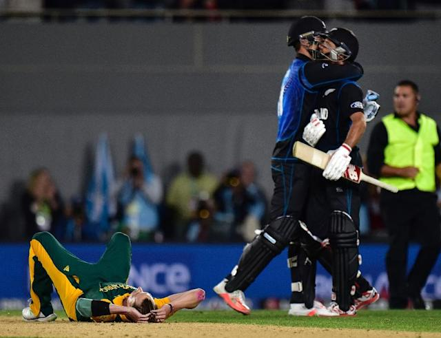 South African bowler Dale Steyn (L) sits dejected after his team's loss as New Zealand batsman Grant Elliott (R) and Daniel Vettori celebrate during the Cricket World Cup semi-final match in Auckland on March 24, 2015 (AFP Photo/Marty Melville)