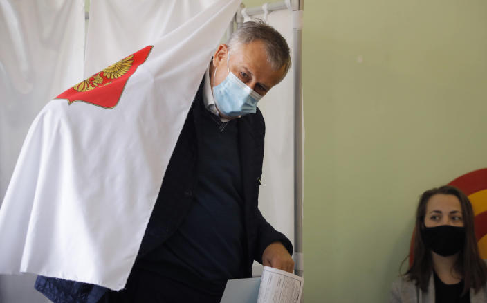 Alexander Drozdenko, governor of Leningrad Region wearing a face mask to protect against coronavirus infection leaves a voting booth at a poling station during Leningrad region's governor and municipal elections in Luppolovo village, outside St. Petersburg, Russia, Sunday, Sept. 13, 2020. Leningrad region is the territory surrounding St. Petersburg. Elections are being held to choose governors and legislators in about half of Russia's regions. (AP Photo/Dmitri Lovetsky)