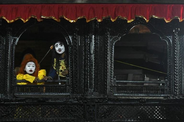 Young artists with painted face look out from a window before performing in a play for the Indra Jatra Hindu festival in Kathmandu, Nepal (AFP Photo/PRAKASH MATHEMA)