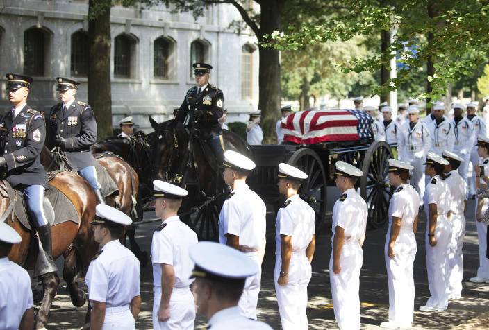 In this image provided by the family of John McCain, the horse-drawn caisson bearing the body of Sen. John McCain, R-Ariz., moves through the grounds of the United Sates Naval Academy toward the cemetery after a service in the Chapel Sunday, Sept. 2, 2018, in Annapolis, Md. (David Hume Kennerly/McCainFamily via AP)