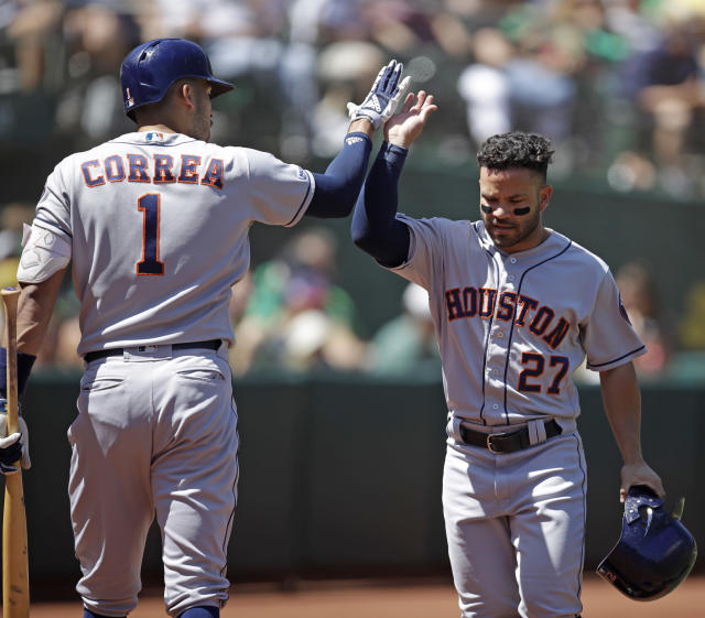 Houston Astros' Jose Altuve, right, is congratulated by Carlos Correa (1) after scoring against the Oakland Athletics in the third inning of a baseball game Saturday, Aug. 17, 2019, in Oakland, Calif. (AP Photo/Ben Margot)