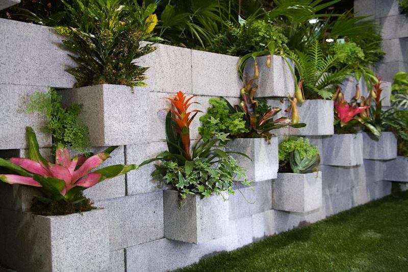 """In this publicity photo provided by Chris H. Olsen, the Landscape Designer, Olsen, of Little Rock, Ark., created a decorative wall out of concrete blocks planted with ivy and tropical plants. Cement couches, benches and tables also can be made by stacking concrete blocks. """"You don't even have to mortar it,"""" he says. Olsen shares more outdoor decorating ideas in his book """"Chris H. Olsen's Five Seasons"""" (Leisure Arts, 2011). (AP Photo/Chris H. Olsen, Janet Warlick/Camera Work)"""