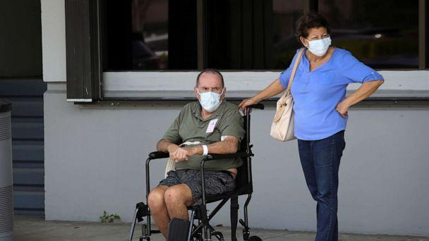 PHOTO: People wearing protective masks are seen outside Jackson Memorial Hospital, as Miami-Dade County eases some of the lockdown measures put in place during the coronavirus disease outbreak, in Miami, June 18, 2020. (Marco Bello/Reuters)
