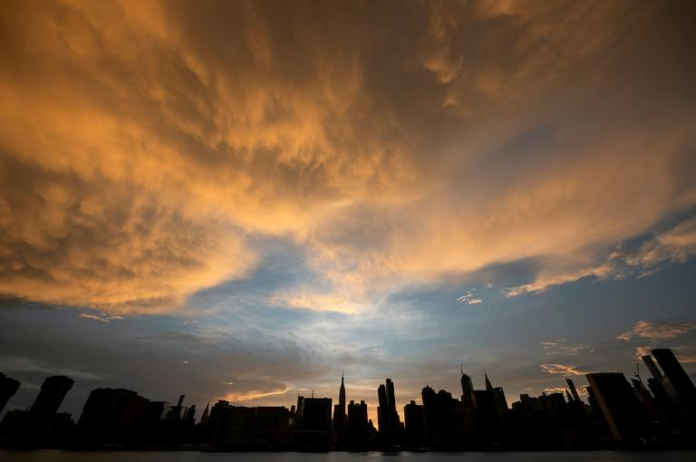 The sun sets behind the skyline of midtown Manhattan in New York City -- rather than falling, the world's carbon dioxide grew two percent in 2018