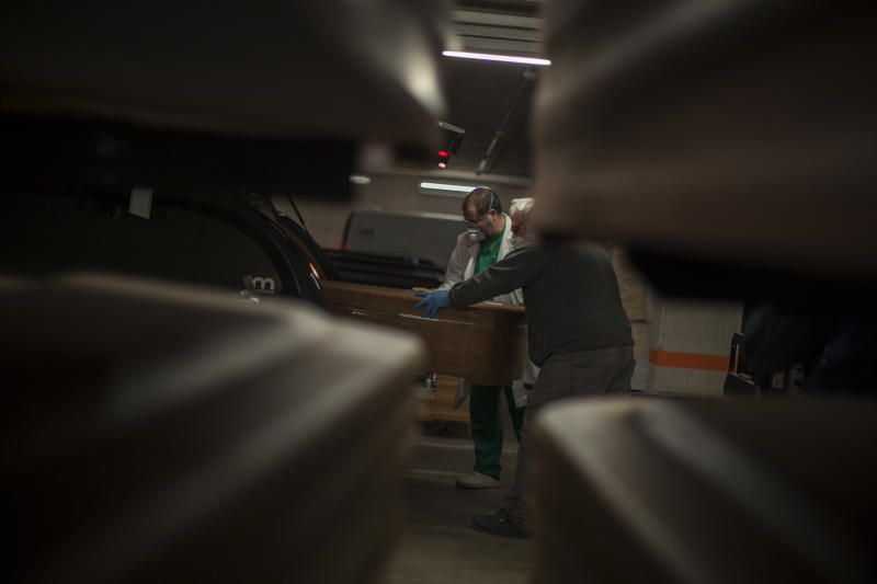 A coffin containing a victim of COVID-19 is loaded into a hurse in the parking garage at the Collserola funeral parlour in Montcada i Reixac, near Barcelona. (José Colon for Yahoo News)