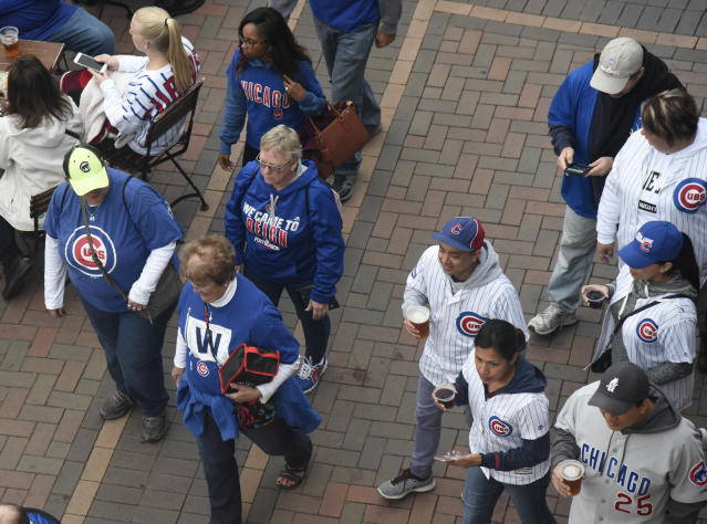 Fans head to the ballpark before the National League wild-card playoff baseball game between the Chicago Cubs and the Colorado Rockies, Tuesday, Oct. 2, 2018, in Chicago. (AP Photo/David Banks)