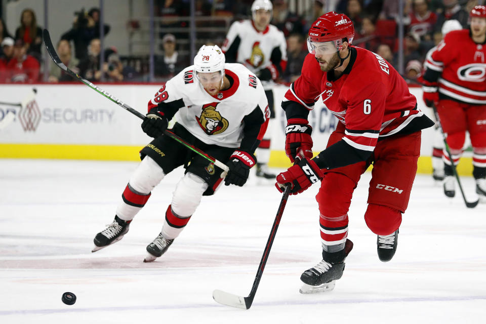 Carolina Hurricanes' Joel Edmundson (6) gathers in the puck in front of a charging Ottawa Senators' Connor Brown (28) during the first period of an NHL hockey game in Raleigh, N.C., Monday, Nov. 11, 2019. (AP Photo/Karl B DeBlaker)