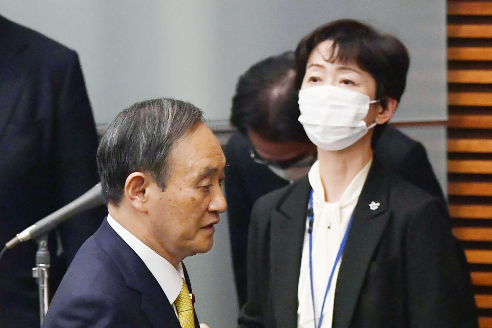 Japanese Prime Minister Yoshihide Suga arrives for a press conference past his cabinet's public affairs official Makiko Yamada, right, at his official residence in Tokyo on Dec. 4, 2020, Yamada, public relations chief for Suga, has resigned Monday, March 1, 2021 after she acknowledged she had a 70,000 yen ($700) dinner paid for by a broadcaster. The broadcaster in question employs Suga's son, Seigo Suga. (Kyodo News via AP)