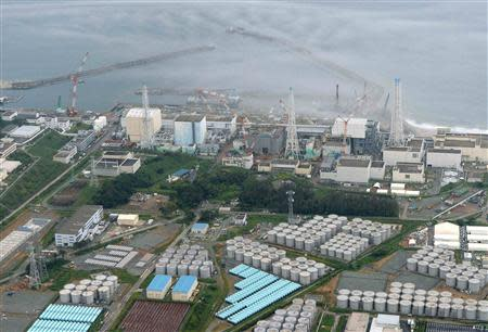 An aerial view shows Tokyo Electric Power Co. (TEPCO)'s tsunami-crippled Fukushima Daiichi nuclear power plant and its contaminated water storage tanks (bottom) in Fukushima in this file photo taken by Kyodo on August 20, 2013. REUTERS/Kyodo/Files