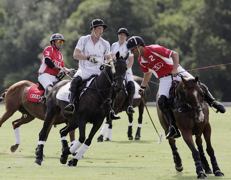 Britain's Prince Harry, front centre, in action with Prince William, behind centre, as they play in the Audi Polo Challenge charity polo match, at Coworth Park, near Ascot, England, Saturday Aug. 3, 2013. Prince William has made his first public appearance since leaving hospital with his newborn son, playing in a charity polo match alongside brother Prince Harry. (AP Photo / Jane Mingay)