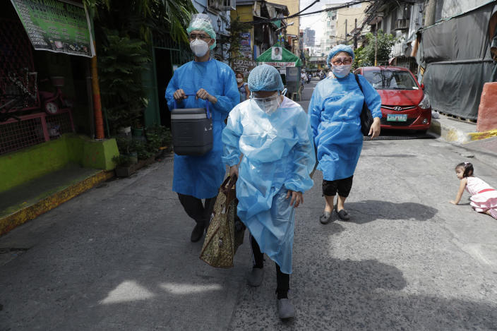 Health workers in protective suits walk to the homes of residents who are not able to go to vaccination centers in Manila, Philippines on Wednesday, May 19, 2021. Philippine President Rodrigo Duterte has eased a lockdown in the bustling capital and adjacent provinces to fight economic recession and hunger but has still barred public gatherings this month, when many Roman Catholic festivals are held. (AP Photo/Aaron Favila)