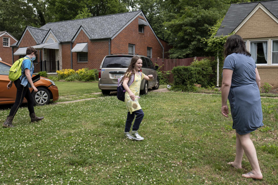 Abby Norman greets her daughters Juliet, 11, left, and Priscilla, 9, as they arrive home from school to the family's Decatur, Ga. home on Tuesday, May 18, 2021. Priscilla was in tears the first morning of testing this year because she felt pressure to do well, but didn't feel prepared after remote learning. (AP Photo/Ben Gray)