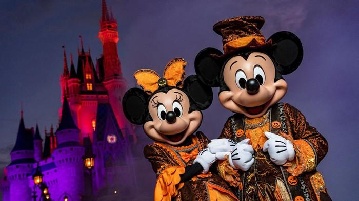 Mickey and Minnie in black-and-orange costumes in front of Cinderella's Castle.