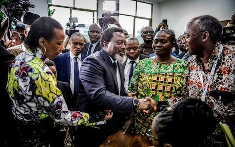 Joseph Kabila greets some electoral observers after casting his vote, December 30  - Credit: LUIS TATO /AFP