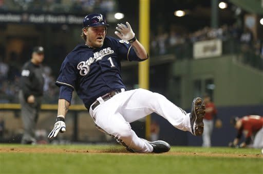 Milwaukee Brewers' Corey Hart slides into third base with a triple against the Houston Astros during the fourth inning of a baseball game Monday, April 23, 2012, in Milwaukee. (AP Photo/Jeffrey Phelps)