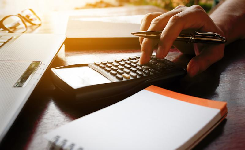 Hand holding pen and typing on calculator that's on a desk next to a steno pad and a computer.