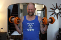 Christian Hainds performs curls as he works out at his home in Hammond, Ind., Monday, June 7, 2021. Health officials have warned since early on in the pandemic that obesity and related conditions such as diabetes were risk factors for severe COVID-19. It wasn't until he was diagnosed as diabetic around the start of the pandemic that he felt the urgency to make changes. Hainds lost about 50 pounds during the pandemic, and at 180 pounds and 5 feet, 11 inches tall is no longer considered obese. (AP Photo/Shafkat Anowar)