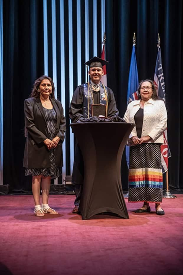 Chase Soosay receives the President's Medal during his MacEwan University convocation in July. Standing beside him are his aunt Gilda Soosay, left, and mother Violet Soosay, right. (Submitted by Allan Linklater - image credit)