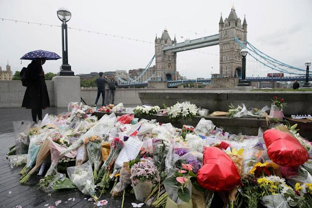 <p>A woman at looks at flowers placed for attack victims at Potters Field Park in London, Tuesday, June 6, 2017. (Photo: Tim Ireland/AP) </p>