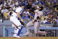 San Francisco Giants' Donovan Solano, right, scores on a double by Thairo Estrada as Los Angeles Dodgers catcher Will Smith waits for the ball during the seventh inning of a baseball game Monday, July 19, 2021, in Los Angeles. (AP Photo/Mark J. Terrill)