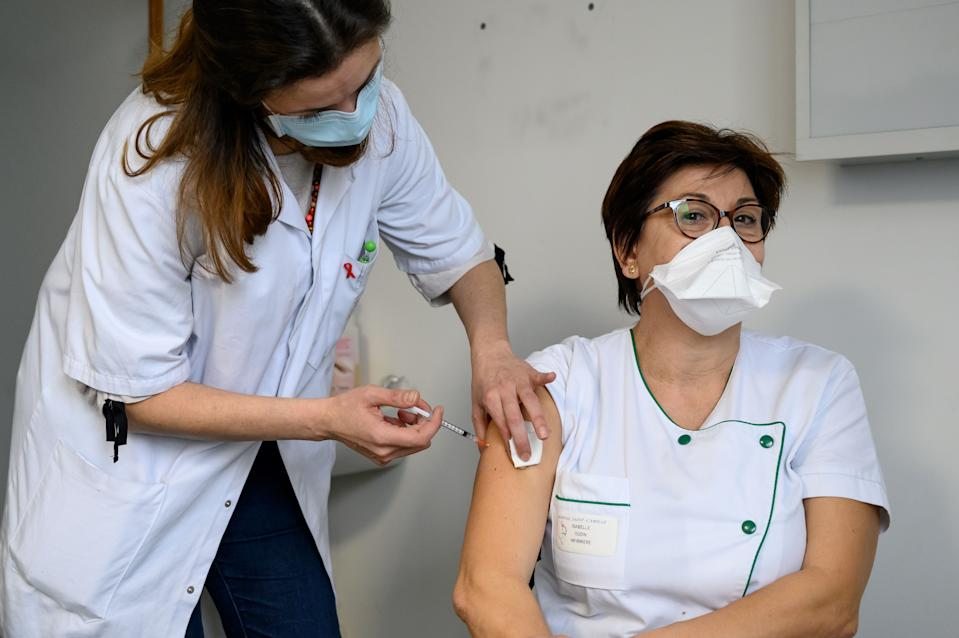A caregiver receives the Pfizer-BioNTech Covid-19 vaccine at the Saint-Camille hospital in Bry-sur-Marne, on January 8, 2021. - France began its Covid-19 vaccination campaign on December 27, 2020 to fight against the spread of the novel coronavirus. (Photo by BERTRAND GUAY / AFP) (Photo by BERTRAND GUAY/AFP via Getty Images)
