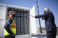 Gov. Jay Inslee, right, speaks to principal engineer Scott Gibson about the Microgrid batteries Tuesday, April 20, 2021, in Arlington, Wash. (Olivia Vanni/The Herald via AP)