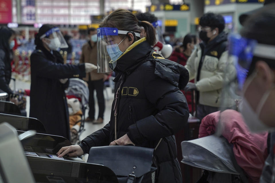 A woman wearing a face mask and face shield to help curb the spread of the coronavirus prepares to board her train at the South Train Station in Beijing, Thursday, Jan. 28, 2021. Efforts to dissuade Chinese from traveling for Lunar New Year appeared to be working. Beijing's main train station was largely quiet on the first day of the travel rush and estimates of passenger totals were smaller than in past years. (AP Photo/Andy Wong)
