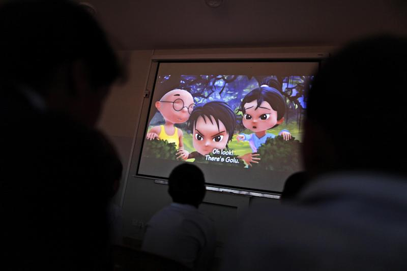In this Monday, March 25, 2013 photo, Pakistani orphans watch an early screening of the first episode of the animate Burka Avenger Series, at an orphanage on the outskirts of Islamabad, Pakistan. Wonder Woman and Supergirl now have a Pakistani counterpart in the pantheon of female superheroes _ one who shows a lot less skin. Meet Burka Avenger: a mild-mannered teacher with secret martial arts skills who uses a flowing black burka to hide her identity as she fights local thugs seeking to shut down the girls' school where she works. Sadly, it's a battle Pakistanis are all too familiar with in the real world.(AP Photo/Muhammed Muheisen)