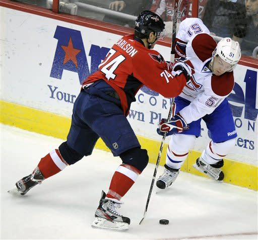 Washington Capitals defenseman John Carlson (74) battles for the puck against Montreal Canadiens center David Desharnais (51) during the first period of an NHL hockey game on Friday, Feb. 24, 2012, in Washington. (AP Photo/Nick Wass)