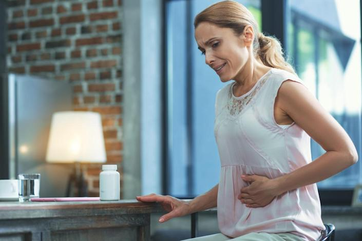 woman in white shirt holding stomach under ribs as if in pain