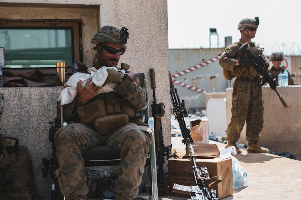A US Marine holds what is believed to be the same baby during the evacuation frenzy.